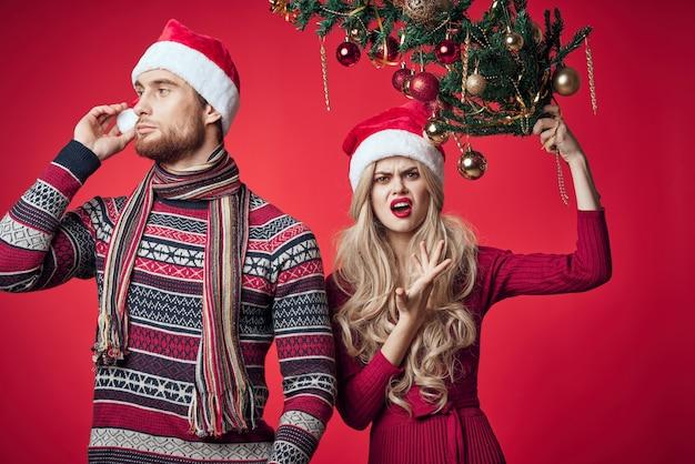 Frau mit einem weihnachtsbaum in ihren händen nahe bei einem mannfeiertagsfamilienweihnachten