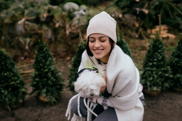 Frau mit einem weißen hund im arm in der nähe von grünen weihnachtsbäumen auf dem markt