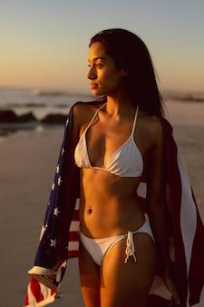 Frau mit einer amerikanischen flagge, die auf dem strand steht
