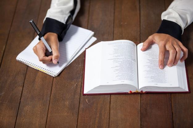 Frau mit einer bibel, die auf notizblock schreibt