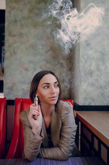 Frau mit einer elektronischen zigarette sitzt