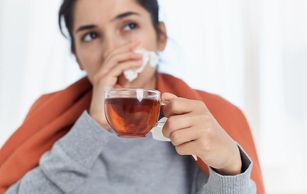 Frau mit einer erkältung in einem orange plaid mit einer tasse tee und einer serviette