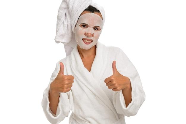 Frau mit einer feuchtigkeitsspendenden stoffmaske im gesicht in einem weißen gewand mit daumen nach oben