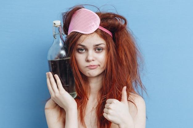 Frau mit einer flasche wodka nach einer party, kater, alkoholismus