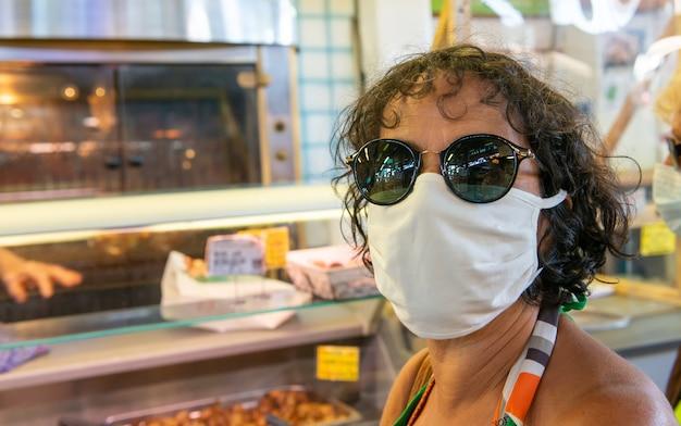 Frau mit einer gesichtsmaske, die am markt einkauft