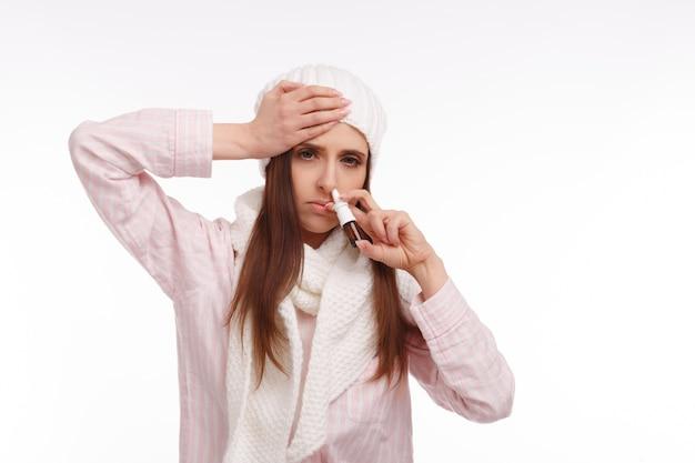 Frau mit einer hand auf dem kopf und einem nasenspray