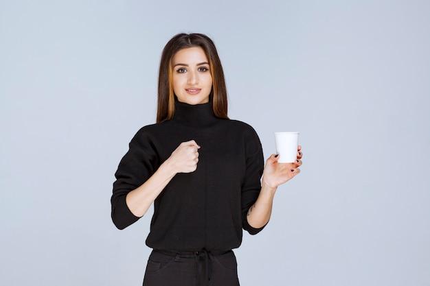 Frau mit einer kaffeetasse, die ihre muskeln zeigt.