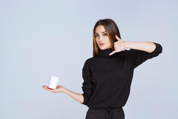 Frau mit einer kaffeetasse, die um einen anruf bittet.