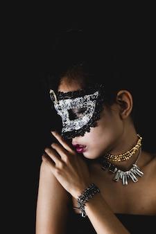 Frau mit einer karnevalsmaske auf einem dunklen hintergrund