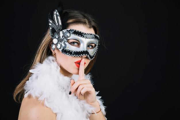 Frau mit einer karnevalsmaske, die ruhegeste auf schwarzem hintergrund macht