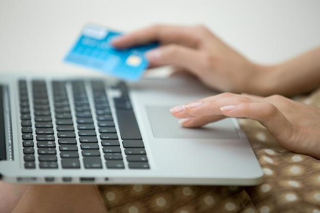 Frau mit einer kreditkarte und einem laptop