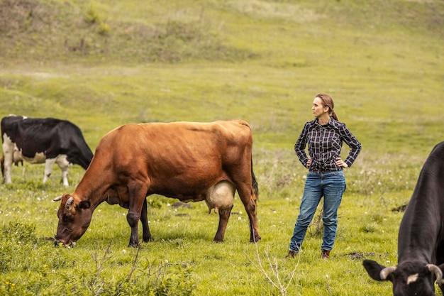 Frau mit einer kuh am bauernhof