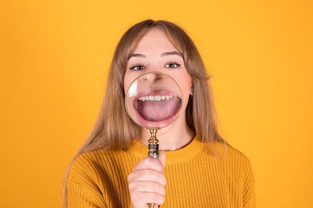 Frau mit einer lupe, die vor ihrem mund, lächeln, lokalisiert auf gelbem hintergrund setzt