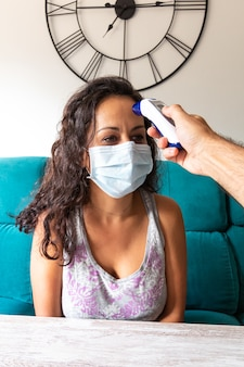 Frau mit einer maske, die ihre temperatur mit einem thermometer zu hause nimmt