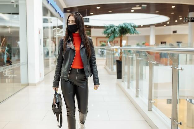 Frau mit einer medizinischen schwarzen maske geht entlang eines einkaufszentrums. coronavirus pandemie. frau in einer schutzmaske kauft im einkaufszentrum ein