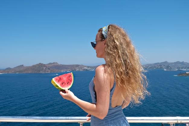 Frau mit einer scheibe wassermelone, die badeanzug meerblick trägt