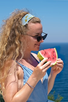 Frau mit einer scheibe wassermelone im badeanzug mit blick auf das meer