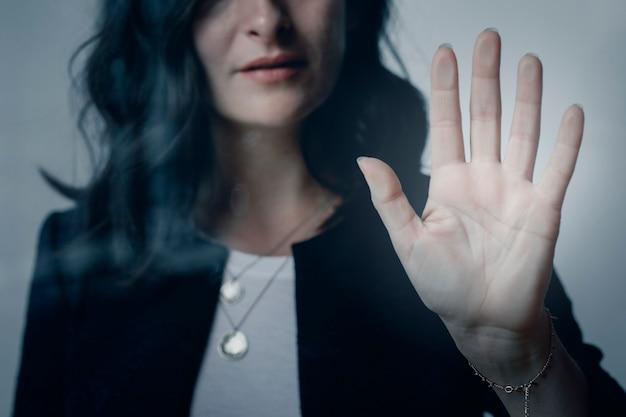 Frau mit einer schönen hand, die das fenster berührt
