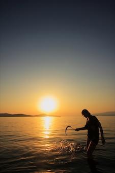 Frau mit einer sichel am strand bei sonnenuntergang