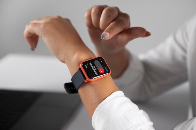 Frau mit einer smartwatch mit digitalem assistenten