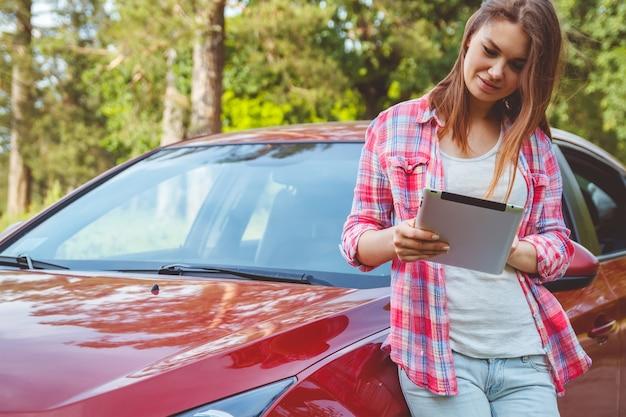 Frau mit einer tablette in den händen, die neben dem auto stehen