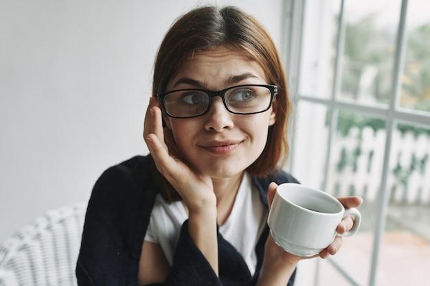 Frau mit einer tasse kaffee innenfenster