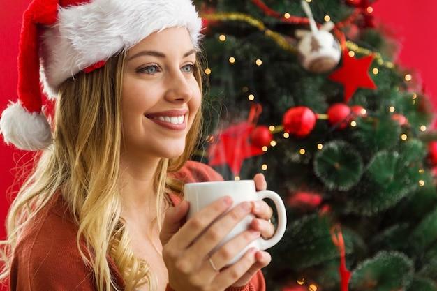 Frau mit einer tasse kaffee lächelnd in die hände
