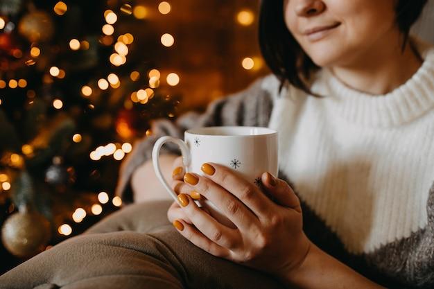 Frau mit einer tasse kaffee oder tee, die auf sofa neben einem weihnachtsbaum zu hause sitzt