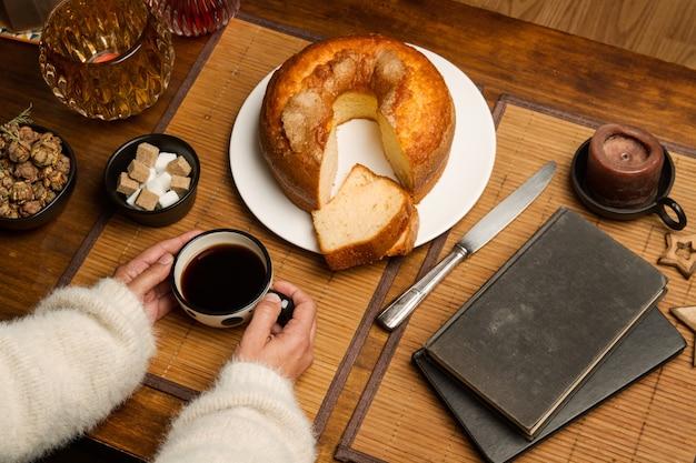 Frau mit einer tasse kaffee und einem vanillekuchen auf einem holztisch