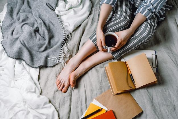 Frau mit einer tasse schwarzen tee und bastelpapier notizbuch in einem bett