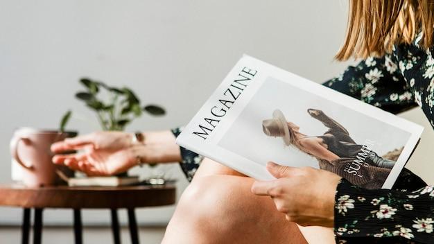 Frau mit einer tasse tee beim lesen einer zeitschrift reading