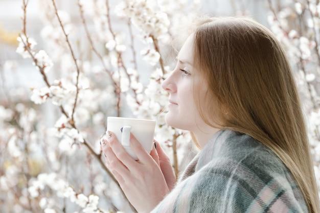 Frau mit einer tasse tee, die am fenster steht und untersucht den abstand. blühender baum