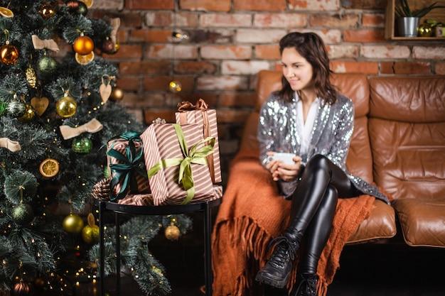 Frau mit einer tasse tee sitzt im wohnzimmer neben weihnachtsbaum und geschenken