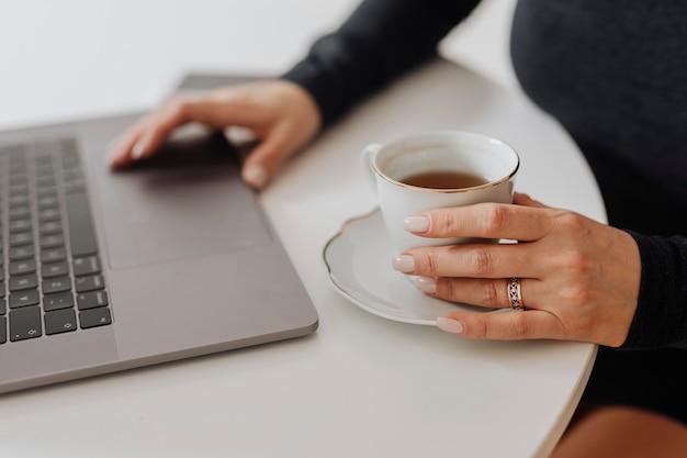 Frau mit einer tasse tee und einem laptop