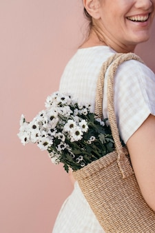 Frau mit einer tüte weißer gänseblümchen