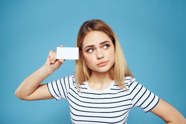 Frau mit einer visitenkarte in ihren händen ein gestreiftes t-shirt blauer kopierraum.