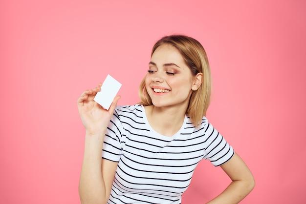 Frau mit einer visitenkarte in ihren händen ein gestreiftes t-shirt rosa copy space werbung.