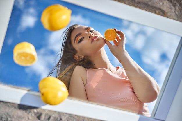 Frau mit einer zitrone in den händen, schönheitshauternährung mit vitamin c. naturkosmetik für die gesichtspflege. sonniger tag blauer himmel