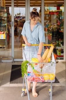 Frau mit einkaufskarten gefüllt mit lebensmitteln, die am sommertag in lässiger blauer kleidung aus dem supermarkt kommen, shopper-konzept