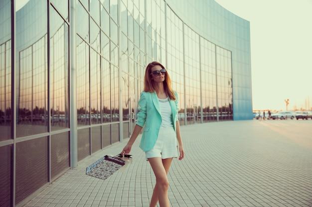 Frau mit einkaufstasche geht den laden entlang