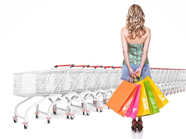 Frau mit einkaufstasche und trolley-wagenhintergrund