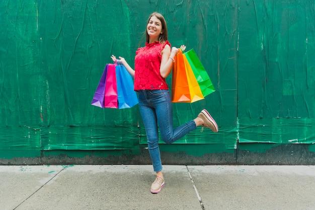 Frau mit einkaufstaschen auf grünem wandhintergrund