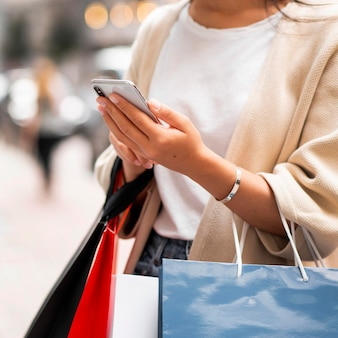 Frau mit einkaufstaschen, die telefon im freien betrachten