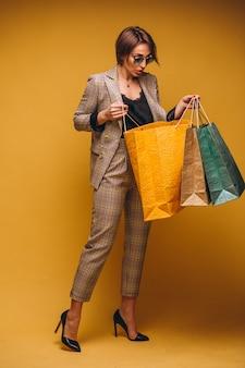 Frau mit einkaufstaschen im studio auf dem gelben hintergrund lokalisiert