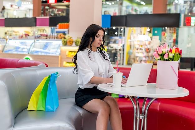 Frau mit einkaufstaschen und laptop im café