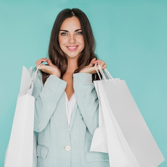 Frau mit einkaufstüten in beiden händen posiert in die kamera