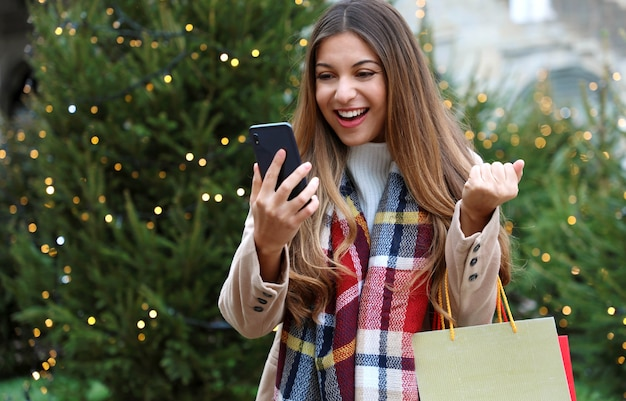Frau mit einkaufstüten in ihrer hand, die weihnachtsgeschenke mit ihrem smartphone kauft