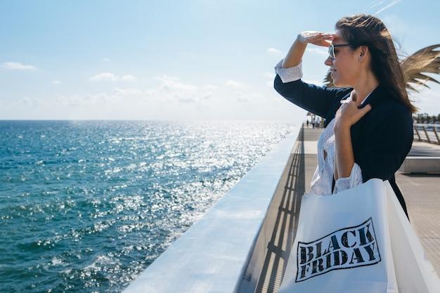 Frau mit einkaufstüten schaut weit weg