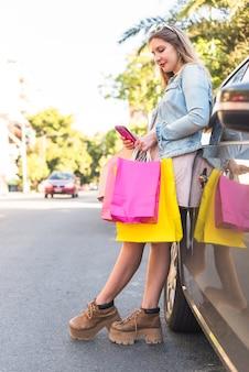 Frau mit einkaufstüten unter verwendung des smartphone am auto