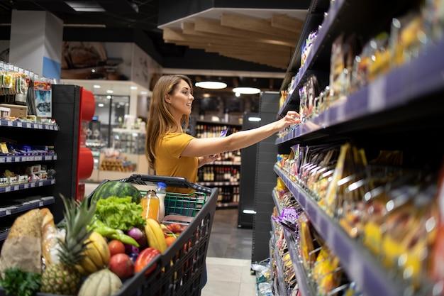Frau mit einkaufswagen, der lebensmittel am supermarkt kauft